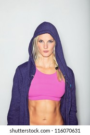 Confident woman in sportswear posing for camera against white background.