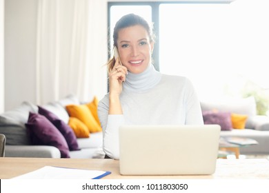 Confident woman talking on her mobile phone and using laptop while sitting at desk and working from home. Home office.
