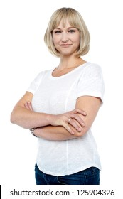 Confident woman in trendy wear with arms folded isolated against white.