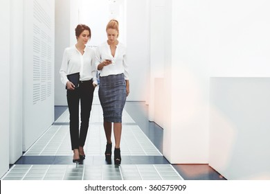Confident women reading information about finance news while walking in company hallway during work break, successful businesswoman writing text message her client while goes with secretary to office