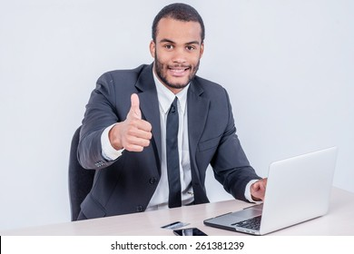 Confident worker business. Smiling businessman sitting at the table and typing a business plan on a laptop while a businessman sitting at a desk and smiling at the camera isolated on a gray background