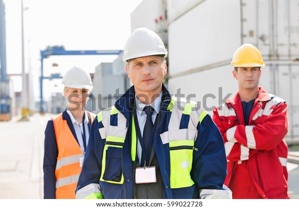 Confident workers standing in shipping yard