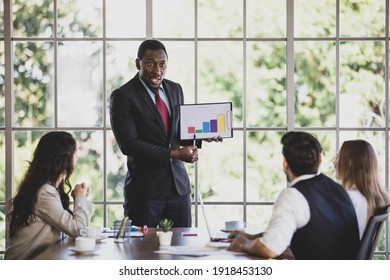 Confident young adult African businessman leader presenting a graph document of their company to caucasian colleagues in meeting to show the financial problem and brainstorm way to solve it