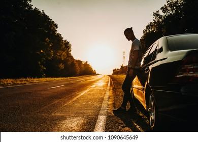 Confident young adventurer, resting leaning on his car against sunset.