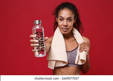 Confident young african american sports fitness woman in sportswear working out isolated on red background. Sport exercises healthy lifestyle concept. Stand with towel over her neck hold water bottle