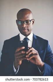 Confident young African businessman wearing a suit and glasses reading text messages on a cellphone while standing alone in an office