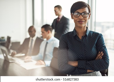 Confident young African businesswoman standing with folded arms smiling at the camera in a boardroom with male colleagues in the background