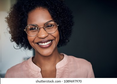 Confident young African businesswoman wearing glasses and laughing while standing alone in a modern office