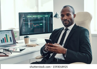 Confident young African man in formalwear looking at camera while working in the office