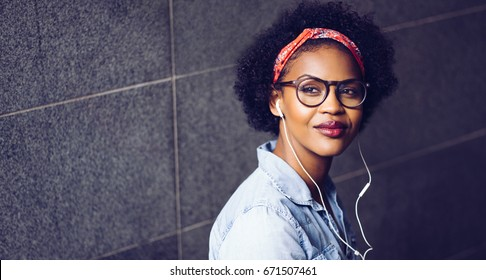 Confident young African woman wearing glasses and a bandana deep in thought while listening to music on earphones