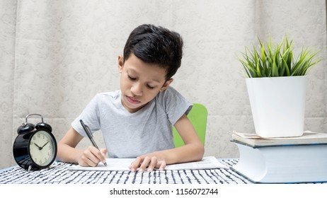 A confident young Asian boy working on his homework - young education concept