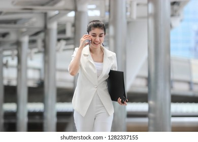 Confident young Asian business woman talking on phone during walking to office.