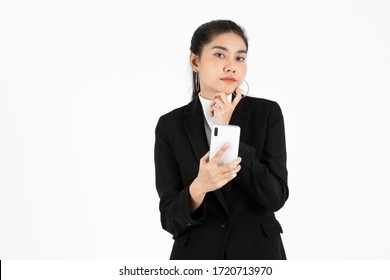 Confident young Asian business woman in suit with mobile smart phone having good idea posing over white isolated background.