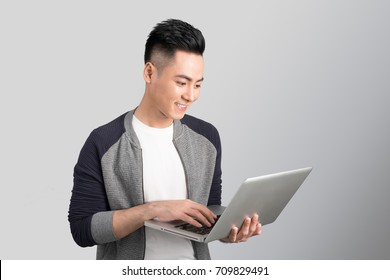 Confident young asian businessman holding laptop