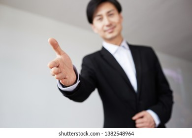 Confident young asian businessman offering handshake after business deal