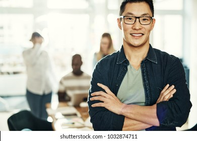 Confident young Asian businessman smiling while standing with his arms crossed in a modern office with colleagues working in the background