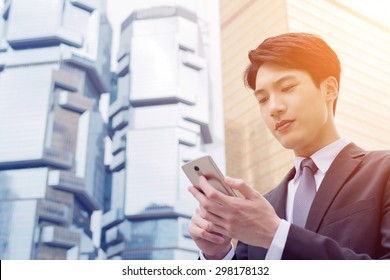 Confident young Asian businessman using cellphone, concept of business, technology, social media etc.