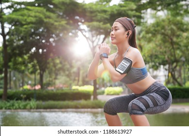 Confident young Asian sportswoman in armband and fitness tracker doing squats and working out in sunlight