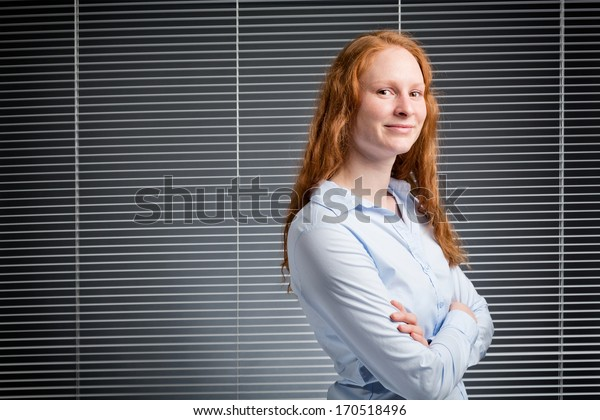 A confident young assistant or a business woman looking at the camera.