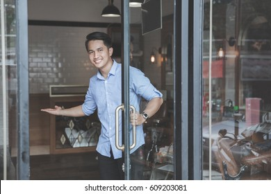 Confident young barber expert smiling welcoming customer to his barbershop