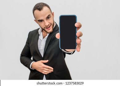 Confident young and bearded man in suit holds phone close to camera. He looks straight. Guy holds another hand on stomach. Isolated on white background.