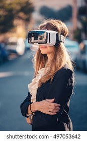 Confident young beautiful girl gesture testing virtual reality 3D video glasses VR headset dressed in a office outfit impressed by augmented reality on the street and beautiful autumn sun light colors