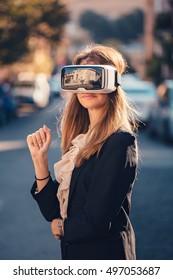 Confident young beautiful girl gesture testing virtual reality 3D video glasses VR headset dressed in a office outfit gesture in the air with the hand touching augmented reality environment