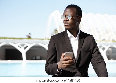 Confident young black businessman formally dressed having round stylish shades holding smart phone messaging online looking aside isolated over urban background. Modern technologies and businesspeople