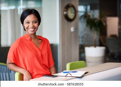 Confident young black entrepreneur smiling at the camera while sitting in a professional colourful business lounge making full eye contact with the camera with a big friendly smile.