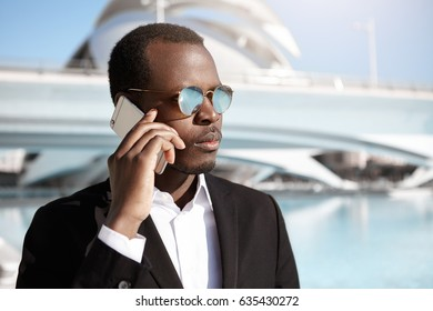 Confident young black European businessman having business negotiations on cell phone, making appointment for meeting with businesspartners while standing in urban setting, looking serious and focused