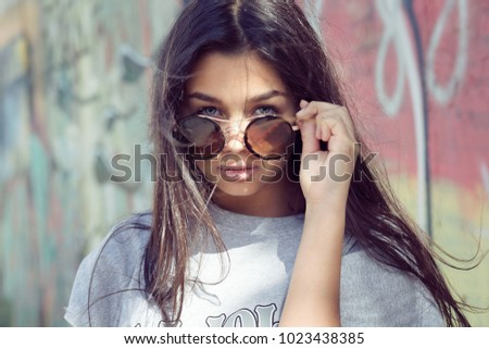 7c29cfa2a8 Confident young brunette in casual t-shirt posing in stylish sunglasses  looking at you camera