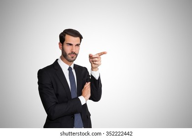 Confident young business man asking money by hand gesture, on gray background.