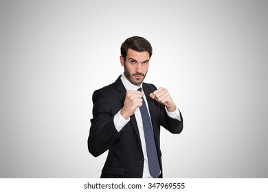 Confident young business man standing in boxer position with fists ready to fight.