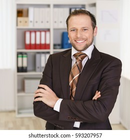 Confident young business manager standing with folded arms in the office looking at the camera with a warm friendly smile