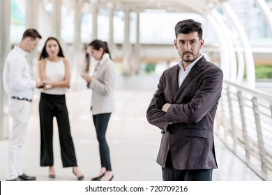 Confident young business team portrait concept. Handsome white male in smart casual dress portrait outdoor with his team in background, successful modern start up concept.