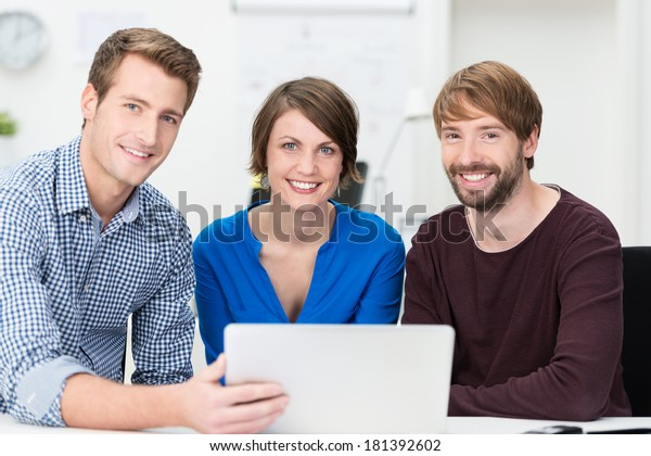 Confident young business team of two men and a woman grouped around a laptop as they sit at a desk in the office together smiling at the camera