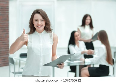confident young business woman with clipboard on the background of business team
