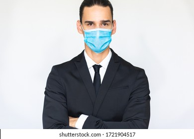 Confident young businessman with arms crossed wearing a blue virus protective medical mask. Isolated portrait looking at the camera.