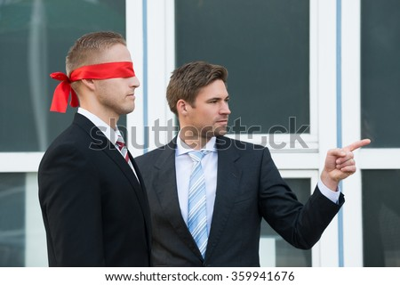 fd4cb056789 Confident young businessman assisting blindfolded partner outside office