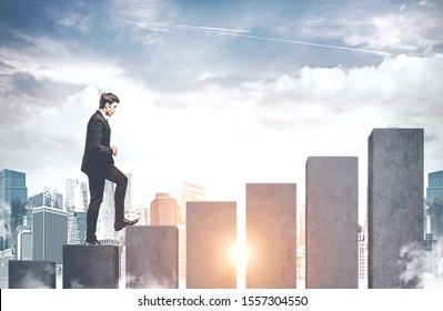 Confident young businessman climbing bar chart in modern city concept of business success and good career. Toned image