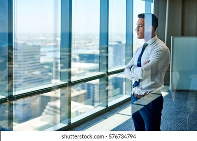 Confident young businessman deep in thought while looking through windows at the city from high up in an office building