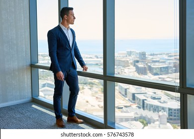 Confident young businessman deep in thought while looking out of windows at the city from high up in an office building