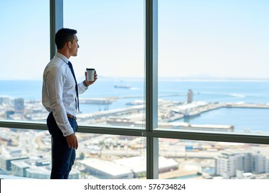 Confident young businessman drinking a cup of coffee while looking through windows at the city from high up in an office building