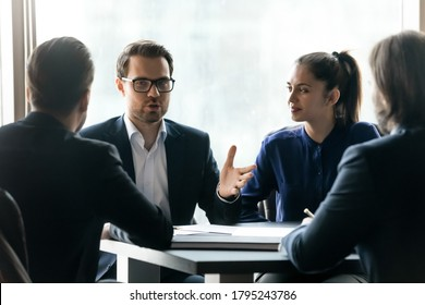 Confident young businessman in eyeglasses holding negotiations meeting with partners in formal wear. Focused diverse employees discussing development strategy or working issues, sitting at table.