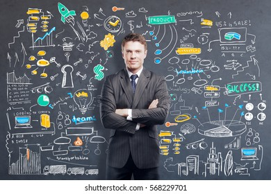 Confident young businessman with folded arms stsnding on grey background with colorful business sketch. Business strategy concept