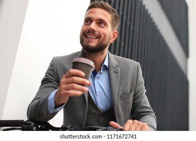Confident young businessman with his bicycle drinking coffee outdoors.