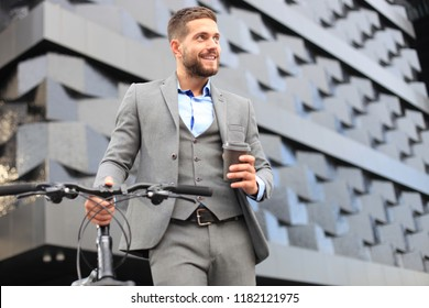 Confident young businessman with his bicycle drinking coffee outdoors