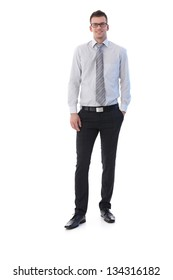 Confident young businessman standing with hands in pocket, smiling.