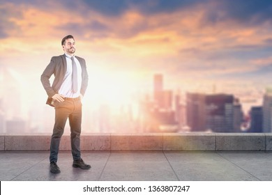 Confident young businessman standing on skyscraper roof with blurred city in background. Concept of leadership. Toned image