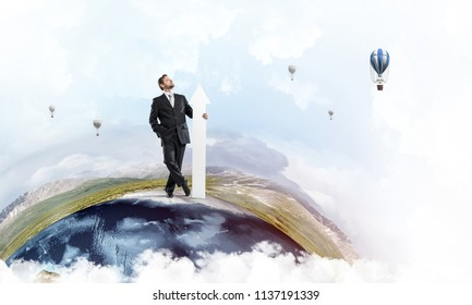 Confident and young businessman in suit holding big white arrow in hand which pointing aside while standing on Earth globe and sky view on background. Elements of this image are furnished by NASA